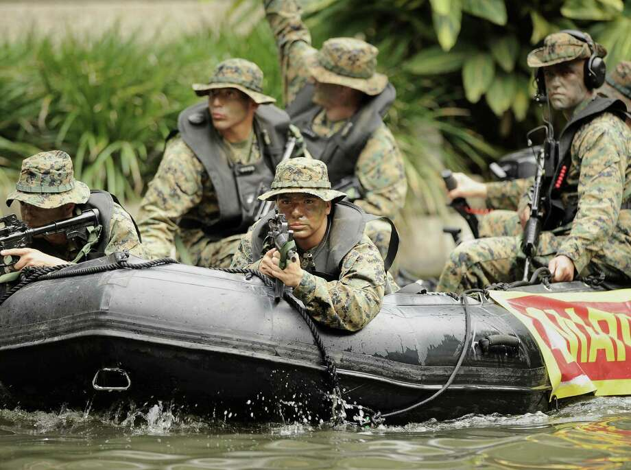 Marines motor through the Rivercenter lagoon in an inflatable boat during America's Armed Forces River Parade last year. Photo: Express-News File Photo / San Antonio Express-News