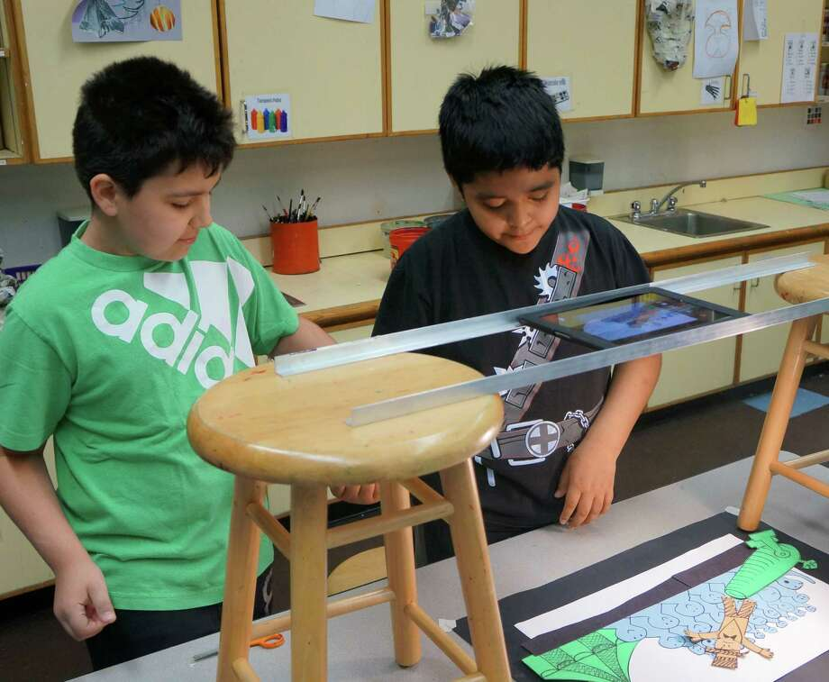 New Lebanon fifth-graders Kevin Dias, left, and Steve Salgado work on a scene before they film it with an iPad. Photo: Paul Schott, Anne W. Semmes / Greenwich Time