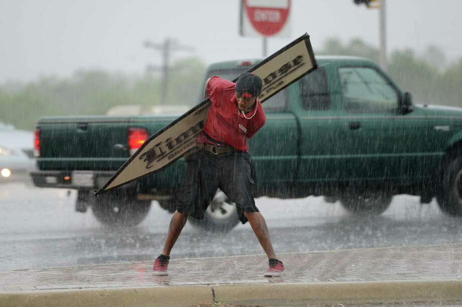 Gloshay Godley braves the rain to  reach customer for the Lions & Rose Pub at the intersection of Loop 410 and Blanco Road on Friday, May 9, 2014. Photo: Billy Calzada, San Antonio Express-News / San Antonio Express-News