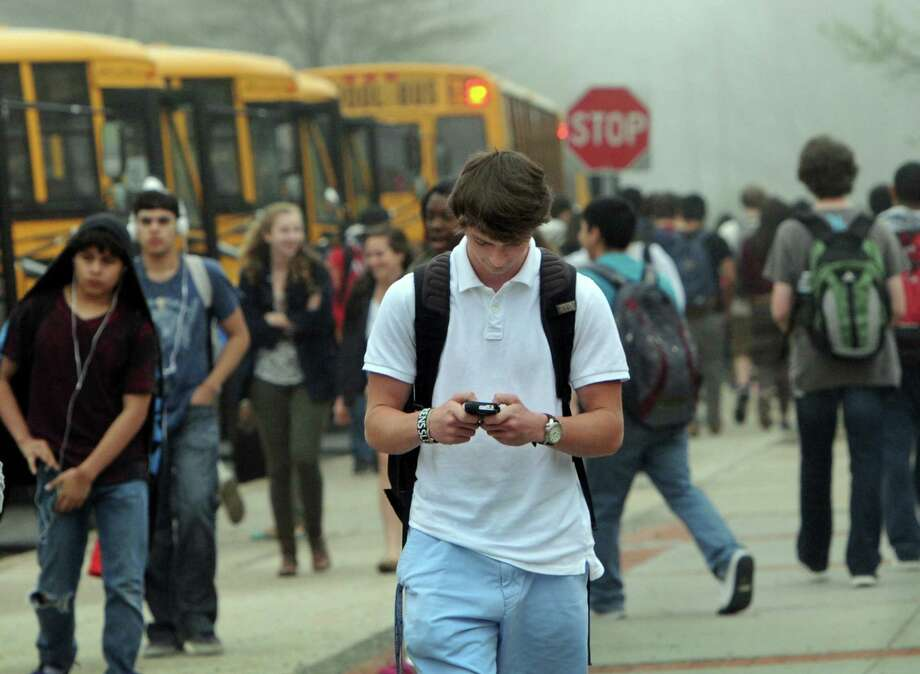 "A student checks his phone at dismissal time at Danbury High School in Danbury, Conn. Friday, May 9, 2014. Some school districts, including Newtown, have decided to erect an invisible ""geo-fence"" around their campuses to prevent students from using Yik Yak, a popular social media app that can be used for anonymous cyberbullying. Photo: Carol Kaliff / The News-Times"