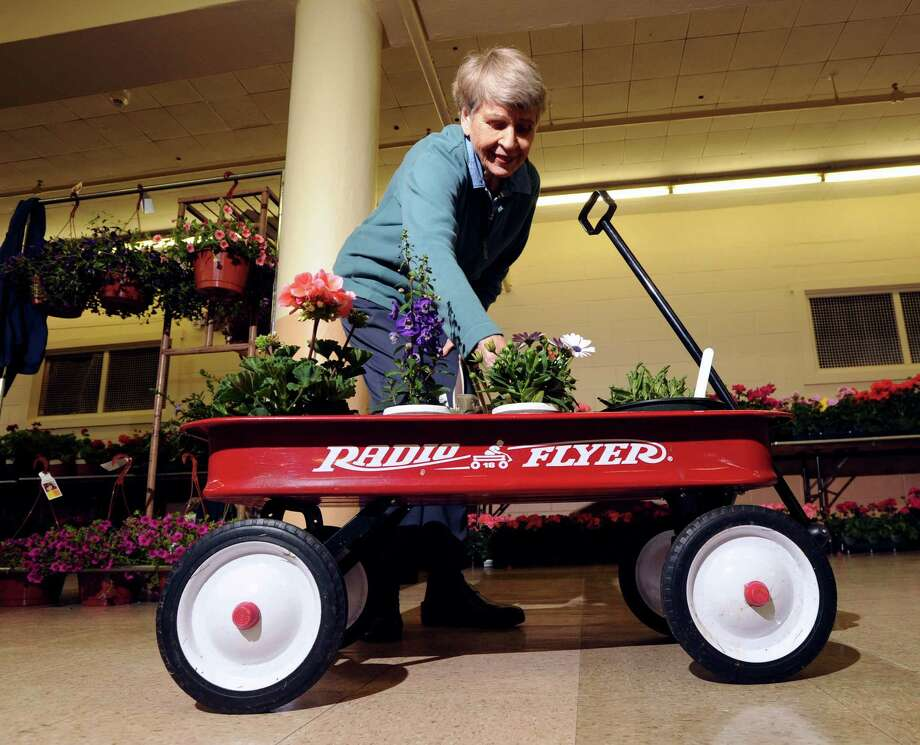 Garden Club of Old Greenwich member Joan Kadlec loads a wagon with flowers at the Greenwich Civic Center, Friday, May 9, 2014. Kadlec was helping to set-up for the club's plant sale held over the weekend. Photo: Bob Luckey / Greenwich Time