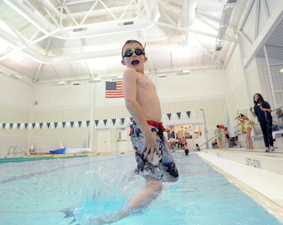Patrick Lane, 8, plunges into the pool during the free swim at the Boys & Girls Club of Greenwich, Friday afternoon, May 9, 2014. Dawn Berrocal, club aquatics director, said the free swim takes place Monday through Friday from 3:30 p.m. to 4:20 p.m. and is open to all club members. Photo: Bob Luckey / Greenwich Time