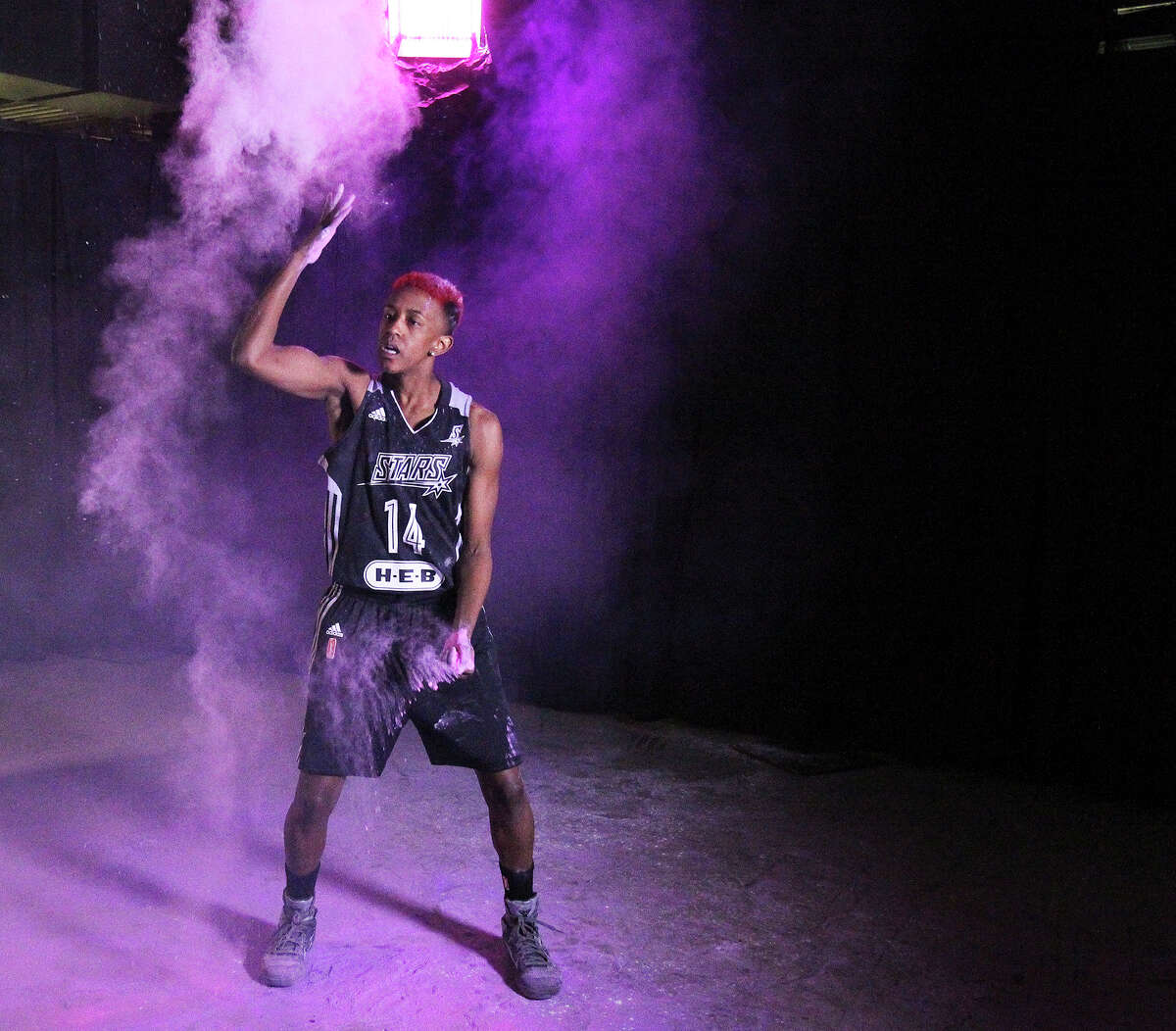 Danielle Robinson sprays powder around the studio as the Stars hold media day at the AT&T Center May 9, 2014.