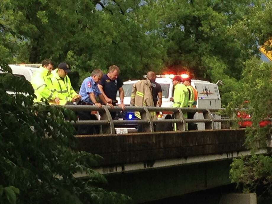 Emergency personnel watch from a bridge on Eisenhauer as others work to recover a body from Salado creek. Photo: Bob Owen/San Antonio Express-News