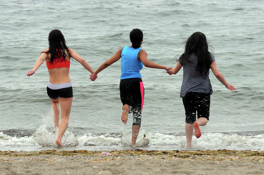 Fairfield Woods students Jasmine Hamel, 14, at left,  Deavionne Ferguson, 14, and Zizi Haidas, 14, hold hands as they run into the chilly water at Jennings Beach in Fairfield, Conn. on Friday May 9, 2014. They are taking part in a new fad among local kids in which friends nominate them to take a polar plunge within 24 hours. They prove they've done so by posting pictures and video clips to Instagram or other social media sites. They in turn nominate other friends to do the same. About 20 kids from the school were on the beach jumping into the water. Photo: Christian Abraham / Connecticut Post