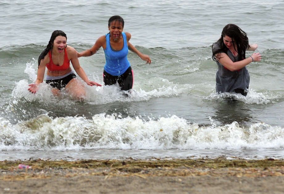 Fairfield Woods students Jasmine Hamel, 14, at left, Deavionne Ferguson, 14, and Zizi Haidas, 14, rush back to shore ater a run into the chilly water at Jennings Beach in Fairfield, Conn. on Friday May 9, 2014. They are taking part in a new fad among local kids in which friends nominate them to take a polar plunge within 24 hours. They prove they've done so by posting pictures and video clips to Instagram or other social media sites. They in turn nominate other friends to do the same. About 20 kids from the school were on the beach jumping into the water. Photo: Christian Abraham / Connecticut Post