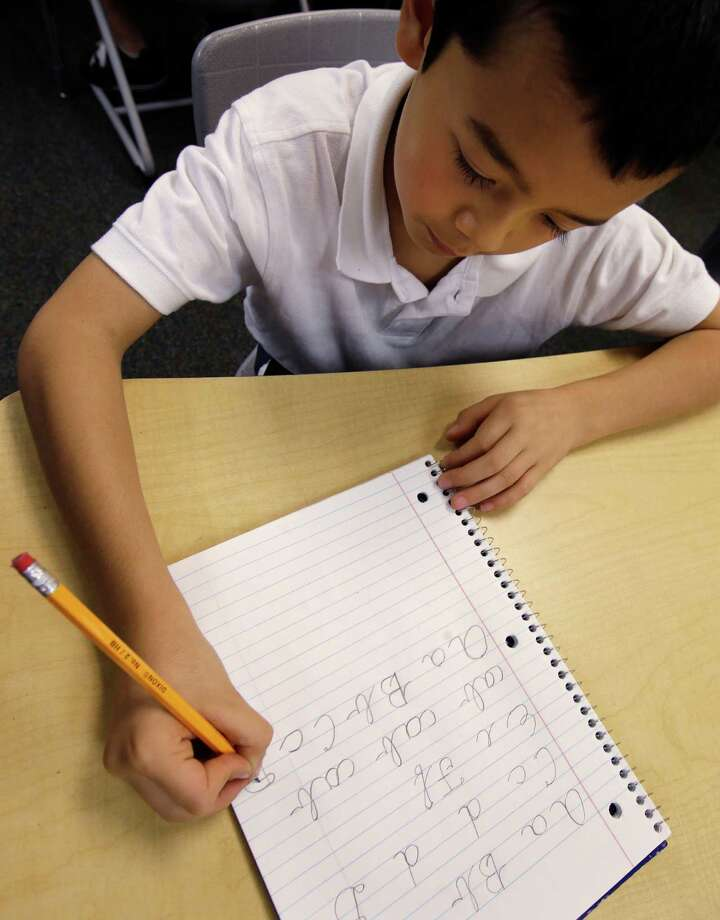 Jaeden Alvarez practices cursive writing at Cleveland K-6 School, Wednesday, Sept. 18, 2013, in Dayton, Ohio. Cursive writing is not being taught in many schools as some 45 states have adopted Common Core standards, which have eliminated the teaching of cursive writing. In years gone by, penmanship helped distinguish the literate from the illiterate. But now, in the digital age, people are increasingly communicating by computer and smartphone. No handwritten signature necessary. Cursive writing is not being taught in many schools as some 45 states have adopted Common Core standards, which have eliminated the teaching of cursive writing. (AP Photo/Al Behrman) Photo: Al Behrman, STF / AP