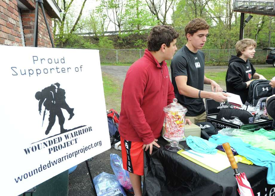At center, Greenwich High School senior Tyler Triscari, 18, sells items to raise money for the Wounded Warrior Project prior to the high school lacrosse match between Greenwich High School and Bronxville High School at Greenwich, on Thursday. Triscari said over the past four years he has raised more than $100,000 for the project that helps wounded soldiers and their families, when the soldiers return from war. Triscari said when he graduates, his brother, Andrew, 14, at left, will be taking over the fundraising activities for the WWP. Photo: Bob Luckey / Greenwich Time