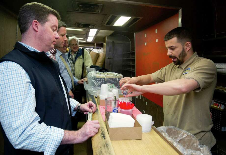 A bartender pour drinks for commuters on a Metro-North bar car on the last night the cars, the last in the country, ran, on Friday, May 9, 2014. Photo: Lindsay Perry / Stamford Advocate