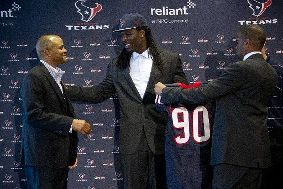 Jadeveon Clowney, center, stands with general manager Rick Smith following a news conference. Photo: Brett Coomer, Houston Chronicle