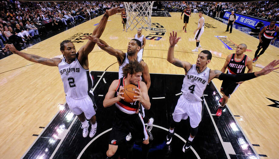 San Antonio Spurs' Kawhi Leonard (from left), Tim Duncan, and Danny Green defend Portland Trail Blazers' Robin Lopez during first half action of Game 2 in the Western Conference semifinals Thursday May 8, 2014 at the AT&T Center. Photo: San Antonio Express-News / © 2014 San Antonio Express-News
