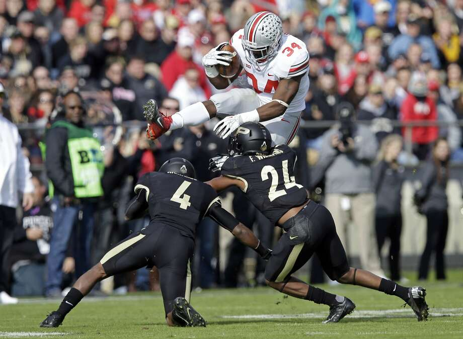 Ohio State running back Carlos Hyde hurdles Purdue's Taylor Richards and Frankie Williams. Photo: Michael Conroy, Associated Press