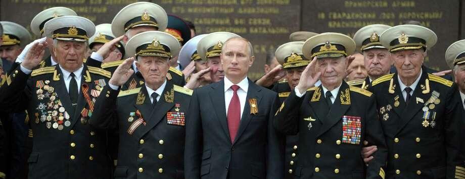Russian President Vladimir Putin and World War II veterans watch a parade in Sevastopol. Photo: Alexey Druzhinin / Getty Images / AFP