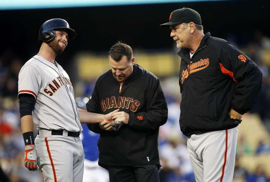 San Francisco Giants' Brandon Belt, left, reacts after being hit by a pitch on his left hand as a trainer and manager Bruce Bochy, right, attend to him against the Los Angeles Dodgers during the second inning of a baseball game, Friday, May 9, 2014, in Los Angeles. (AP Photo/Danny Moloshok) Photo: Danny Moloshok, Associated Press
