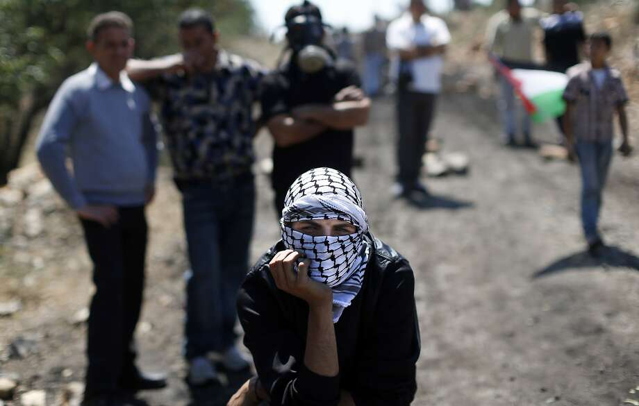 TOPSHOTS A Palestinian protester, with his face covered in a keffiyeh, looks on during clashes with Israeli security forces (unseen) following a weekly protest against the expropriation of Palestinian land by Israel in the West Bank village of Kfar Qaddum, near Nablus on May 9, 2014. AFP PHOTO/ THOMAS COEXTHOMAS COEX/AFP/Getty Images Photo: Thomas Coex, AFP/Getty Images