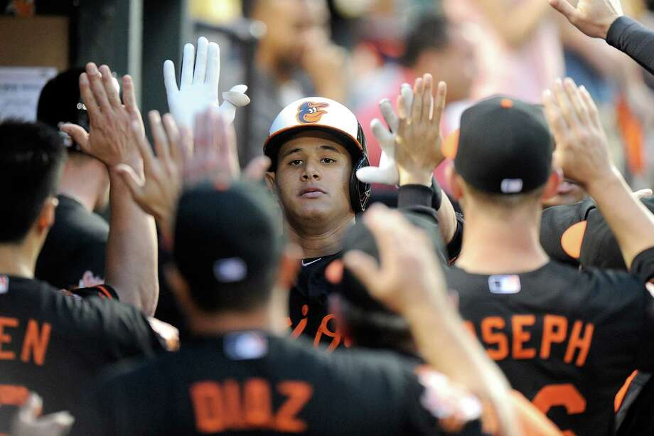Manny Machado shares high-fives with teammates in Baltimore's dugout after homering vs. Houston. Photo: Greg Fiume / Getty Images / 2014 Getty Images