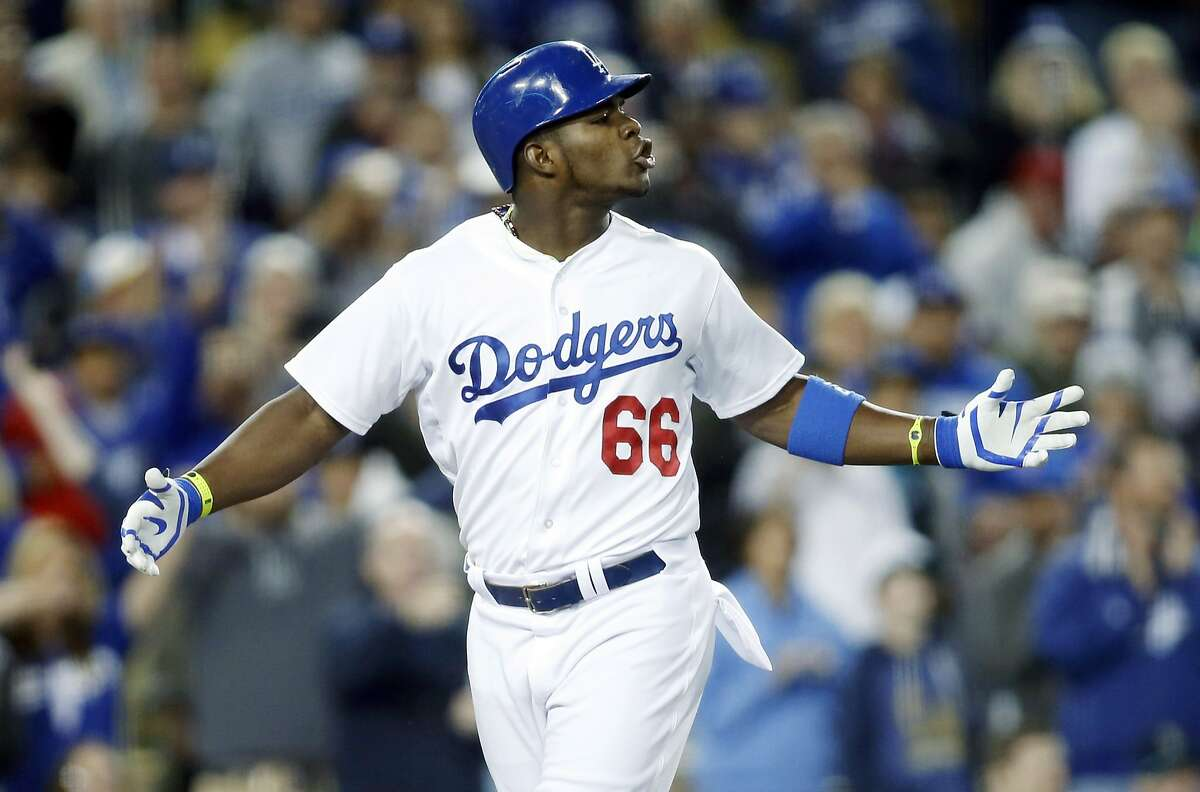 Los Angeles Dodgers' Yasiel Puig exchanges words with San Francisco Giants starting pitcher Madison Bumgarner as Puig runs down the third base line after hitting a solo home run during the sixth inning of a baseball game, Friday, May 9, 2014, in Los Angeles. (AP Photo/Danny Moloshok)