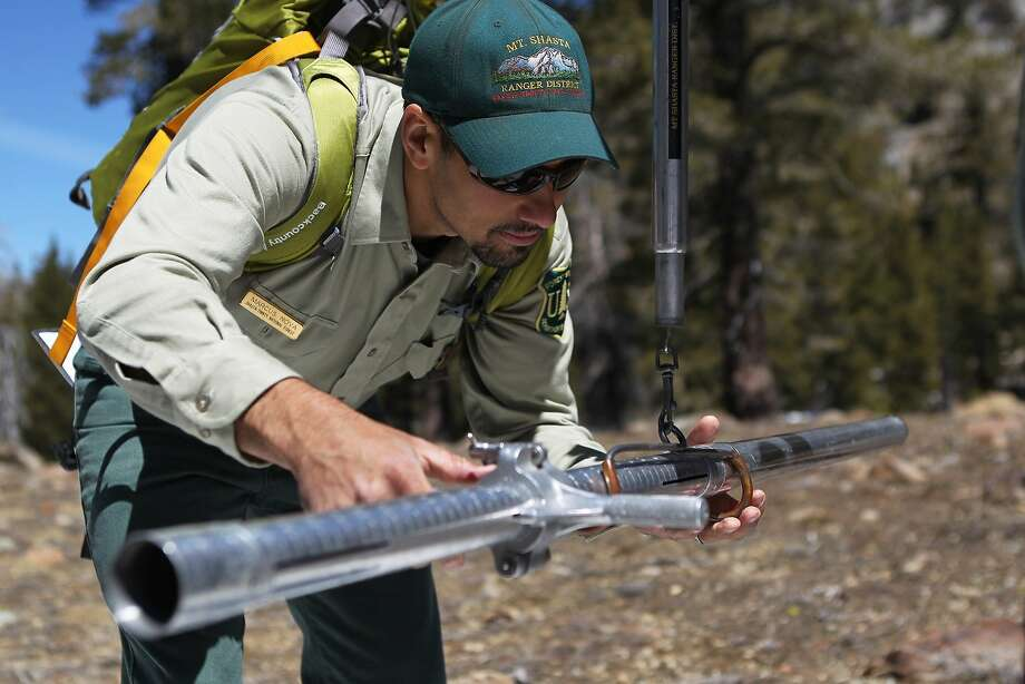 U.S. Forest Service Assistant Resource Officer Marcus Nova weighs a snow tube while conducting a snow survey near Deadfall Lakes outside of Mount Shasta, Calif., on  April 29, 2014.  The drought as left snow levels significantly lower than usual.  (AP Photo/The Record Searchlight,  Andreas Fuhrmann) Photo: Andreas Fuhrmann, Associated Press
