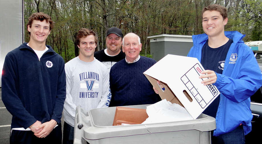 Staples High School's Service League of Boys members Sam Ahlgrin, Kevin Watt and Carl Amacker flank First Selectman Jim Marpe as they help unload his personal papers for Shred Day disposal as technician Allan Perley looks on Saturday. Photo: Mike Lauterborn / Westport News