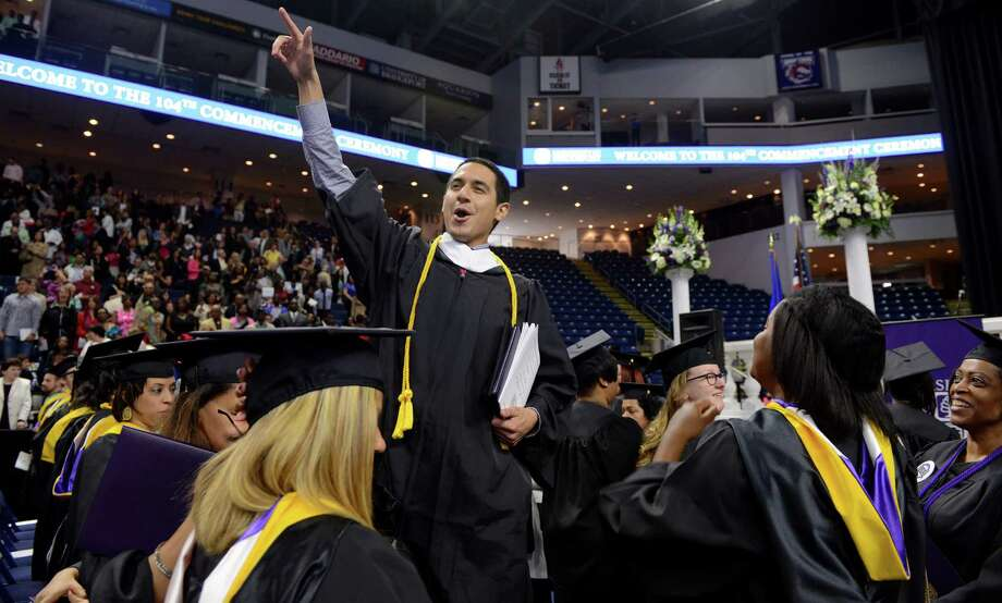 "Michael Martinez, of Greenwich, leads fellow graduates in chanting ""UB"" during the University of Bridgeport's 104th Commencement Ceremony Saturday, May 10, 2014, at the Webster Bank Arena in Bridgeport, Conn. Photo: Autumn Driscoll / Connecticut Post"