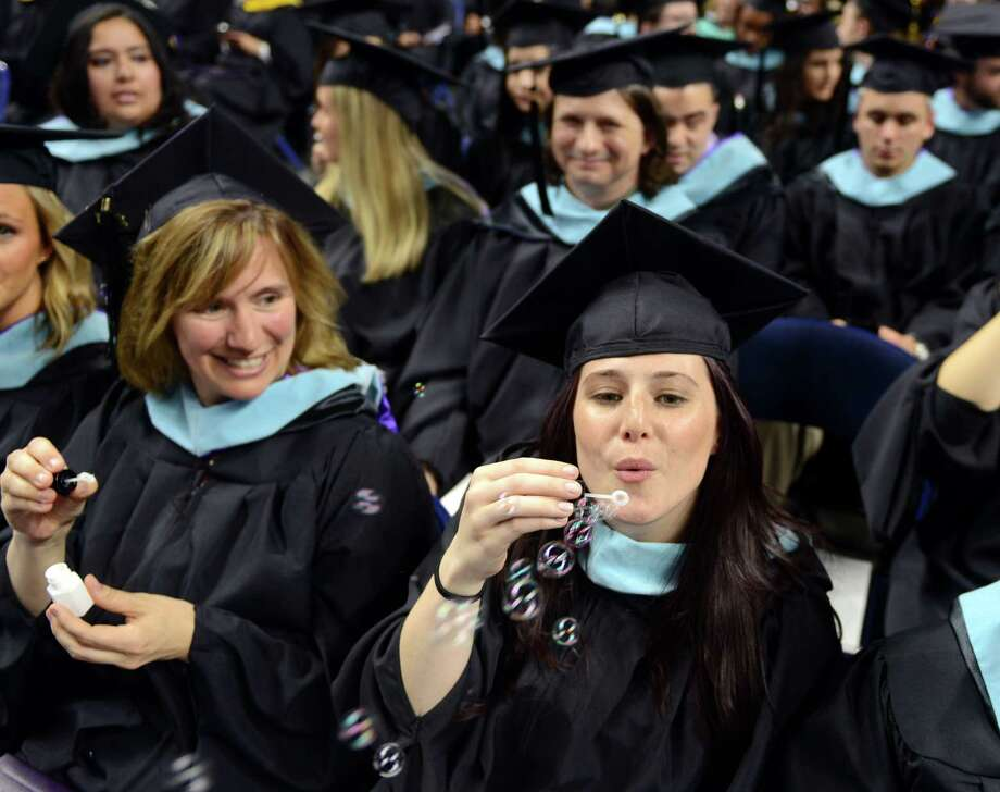 Carolyn Gilland, of Middlebury, blows bubbles during the University of Bridgeport's 104th Commencement Ceremony Saturday, May 10, 2014, at the Webster Bank Arena in Bridgeport, Conn. Photo: Autumn Driscoll / Connecticut Post