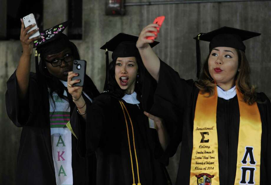 College of Public and International Affairs graduates, from left, Tysheema Doss, of Brooklyn, NY, Jinmee Devine, of Bridgeport, and Katerina Correa, of Queens, NY, take selfies as they wait in line before the University of Bridgeport's 104th Commencement Ceremony Saturday, May 10, 2014, at the Webster Bank Arena in Bridgeport, Conn. Photo: Autumn Driscoll / Connecticut Post