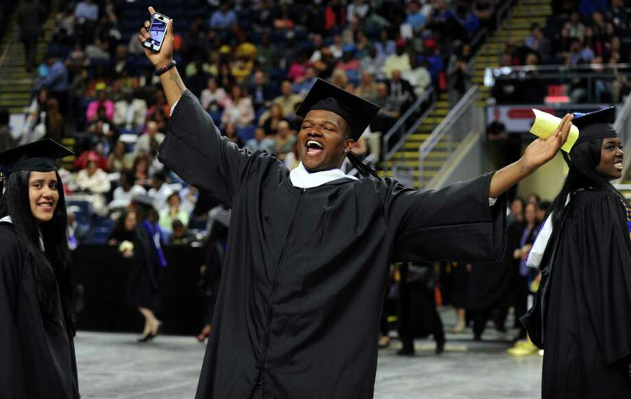 Blake Pierce, of Stratford, gives a big hello to his family in the crowd as he marches into the Webster Bank Arena with his fellow graduates during the University of Bridgeport's 104th Commencement Ceremony Saturday, May 10, 2014. Photo: Autumn Driscoll / Connecticut Post