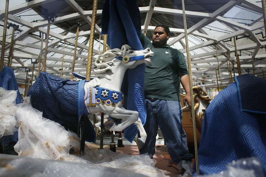 David Finefeviaki unwraps a horse on a 108-year-old carousel that has been mechanically overhauled. Photo: Mike Kepka, The Chronicle