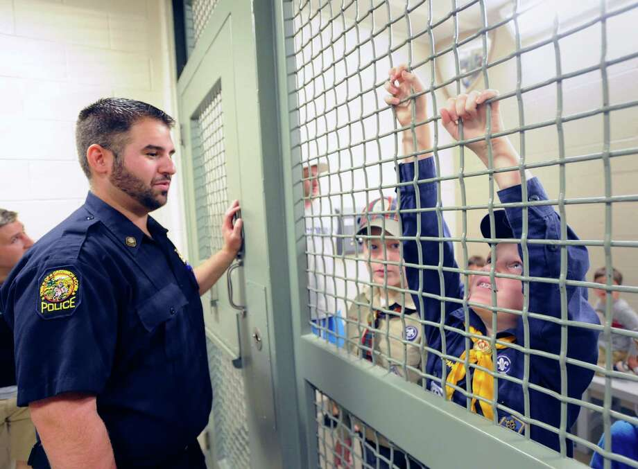 Greenwich Police Officier, Dan Paladino, left, looks on as brothers and Greenwich Cub Scouts, Will Zisson (center), 11, and Doyle Zisson, 8, get to see the inside of a holding cell during a tour of Greenwich Police Headquarters, Saturday morning, May 10, 2014. The guided tour of police headquarters was part of the events put on by the department in honor of National Police Week, May 11- May 17. Photo: Bob Luckey / Greenwich Time