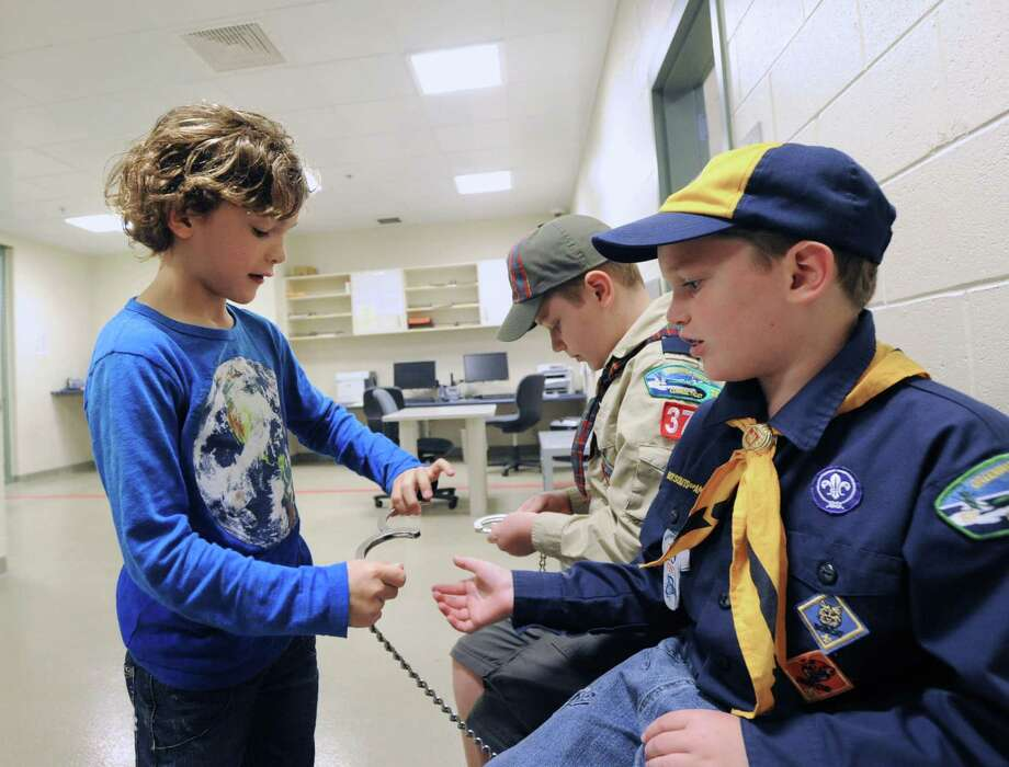 At left, Lenny Lies, 8, of Greenwich, attempts to put a handcuff on Greenwich Cub Scout, Doyle Zisson, 8, right, during a public tour of Greenwich Police Officier, Dan Paladino, gives a tour of Greenwich Police Headquarters, Saturday morning, May 10, 2014. At center is Doyle's brother, Greenwich Cub Scout, Will Zisson, 11. The guided tour of police headquarters was part of the events put on by the department in honor of National Police Week, May 11- May 17. Photo: Bob Luckey / Greenwich Time