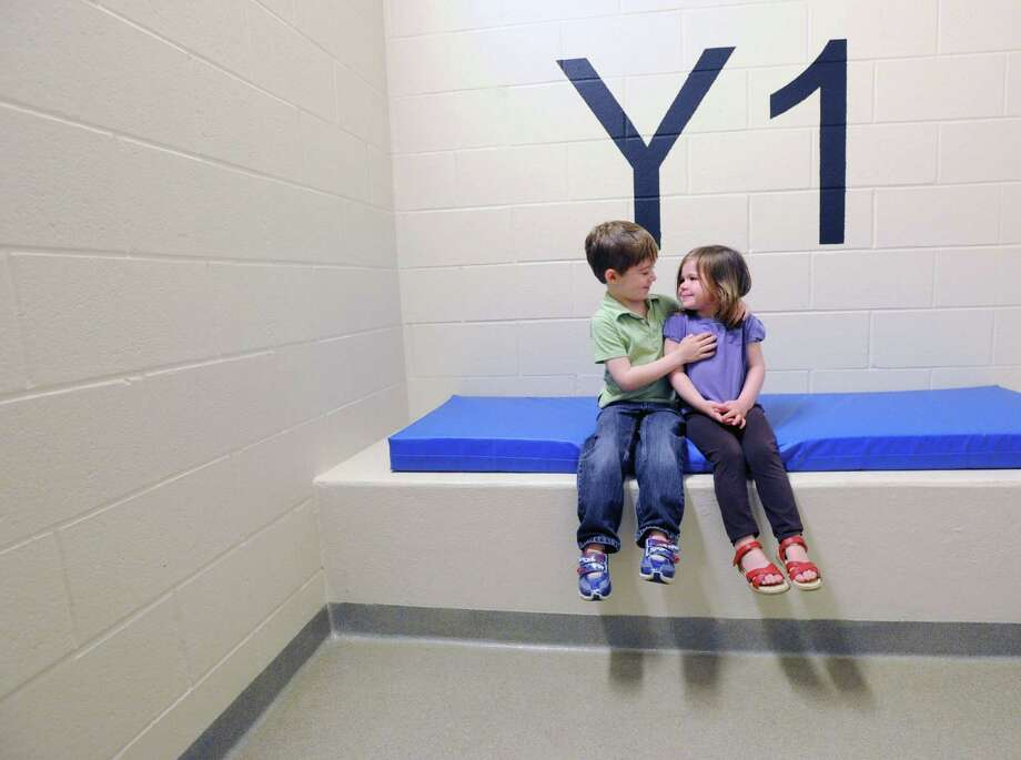 At left, Aidan Delaney, 5, of Greenwich, puts his arm around his sister, Katy Delaney, 3, while the pair got to sit inside a holding cell as part of a tour of of Greenwich Police Headquarters, Saturday morning, May 10, 2014. The guided tour of police headquarters was part of the events put on by the department in honor of National Police Week, May 11- May 17. Photo: Bob Luckey / Greenwich Time