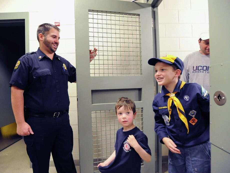 Greenwich Police Officier, Dan Paladino, left, lets Conor O'Brien, 3, at center, and Greenwich Cub Scout, Doyle Zisson, 8, both of Greenwich, out of a holding cell during a tour of Greenwich Police Headquarters, Saturday morning, May 10, 2014. The guided tour of police headquarters was part of the events put on by the department in honor of National Police Week, May 11- May 17. Photo: Bob Luckey / Greenwich Time