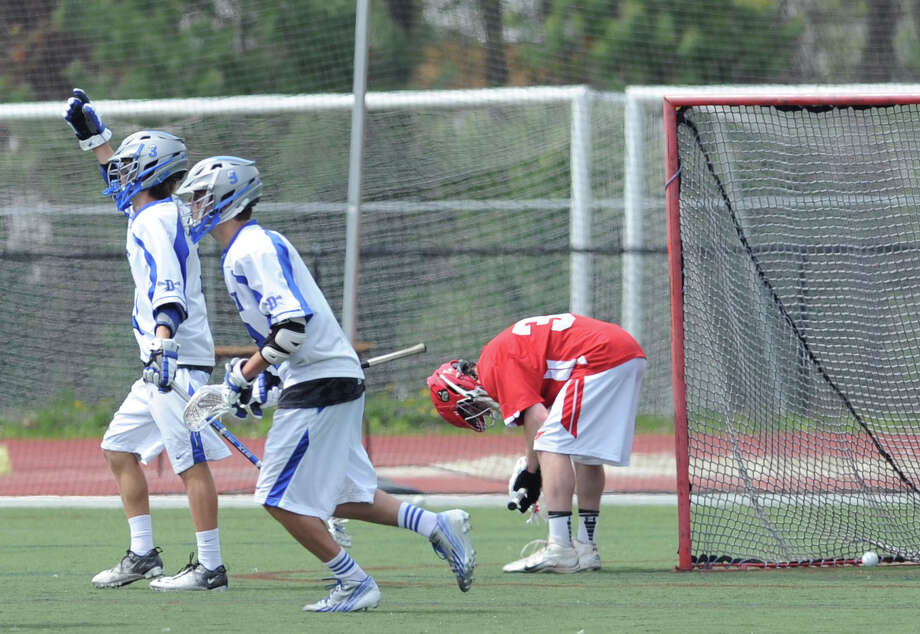 Greenwich goalie Tommy Rogan, right, bows down as the ball shot by Darien's John Reed comes to rest in the net for a 4th quarter goal during the boys high school lacrosse match between Darien High School and Greenwich High School at Darien, Saturday afternoon, May 10, 2014. Celebrating Reed's goal are Darien teammates, Colin Minicus, left, and Owen Koorbusch, center. Darien remained undefeated, winning the match over Greenwich, 10-4. Photo: Bob Luckey / Greenwich Time