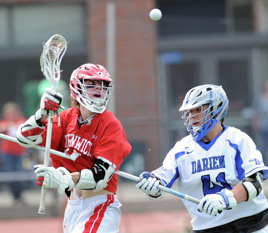 At left, Decker Curran of Greenwich passes while being defended by Darien's Mark Evanchick (#41) during the boys high school lacrosse match between Darien High School and Greenwich High School at Darien, Saturday afternoon, May 10, 2014. Darien remained undefeated, winning the match over Greenwich, 10-4. Photo: Bob Luckey / Greenwich Time