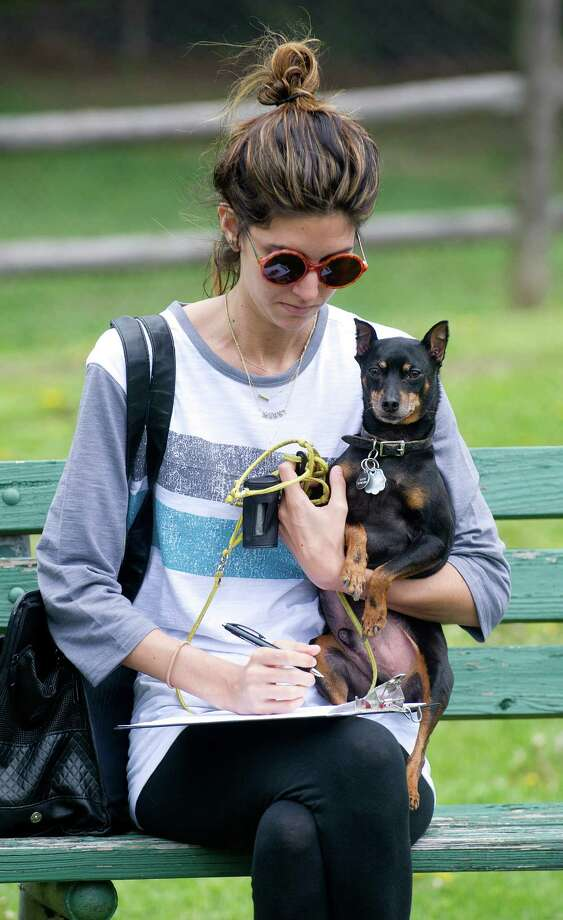 Marki DeSimone holds her Miniature Pinscher, Gotti, as she fills out a form to get a microchip at the Stamford Dog Park on Saturday, May 10, 2014, the 5-year anniversary of the park. Photo: Lindsay Perry / Stamford Advocate