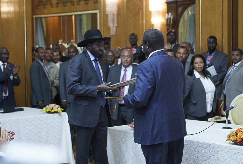 South Sudan President Salva Kiir (left) and ex-Vice President Riek Machar hand over the treaty Friday. Photo: Zacharias Abubeker, AFP/Getty Images