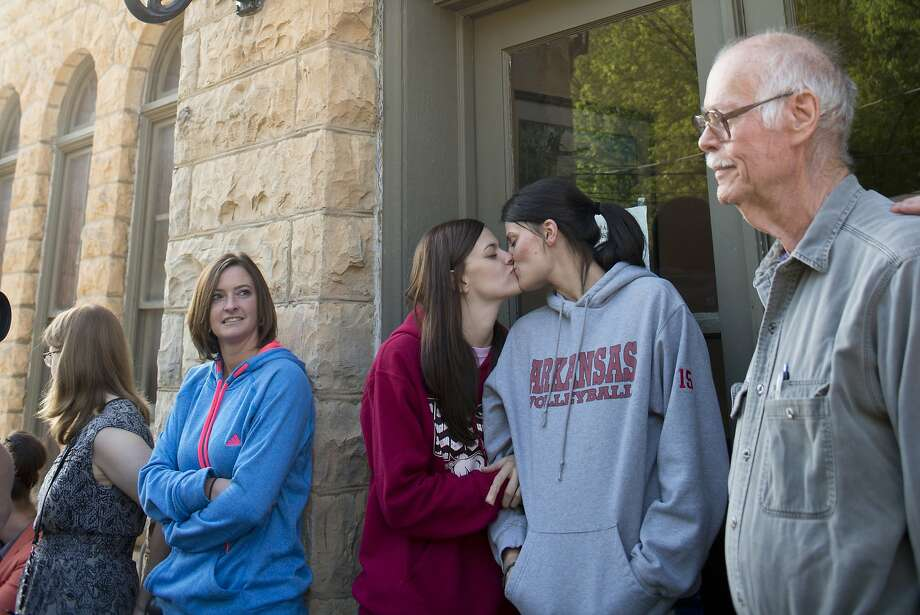 Jennifer Rambo, left, of Jacksonville, Ark., kisses her partner Kristin Seaton, right, of Fort Smith, Ark., as they wait in line at the Carroll County Courthouse to apply for a marriage license, Saturday, May 10, 2014, in Eureka Springs, Ark. Rambo and Seaton drove to Eureka Springs Friday night and slept in their car after a judge overturned Ammendment 83, which banned same-sex marriage in the state of Arkansas. (AP Photo/Sarah Bentham) Photo: Sarah Bentham, Associated Press