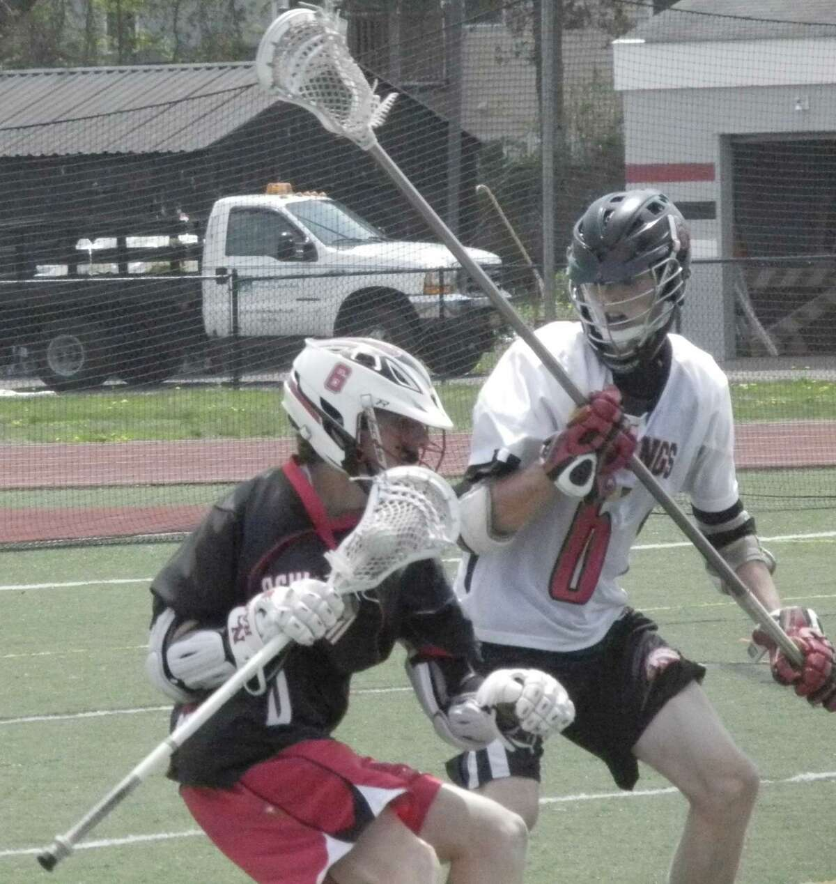 Fairfield Warde's Greg Adams, right, challenges New Canaan's Michael Kraus in an FCIAC boys lacrosse game on Saturday, May 10 at Tetreau/Davis Field in Fairfield. The visiting Rams, in black, defeated the Mustangs 12-4. Kraus scored two goals.