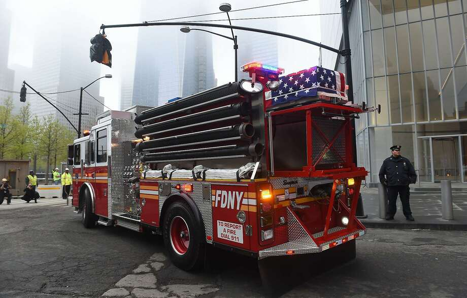 A casket carrying the unidentified remains of victims of the September 11, 2001 attacks sits atop a firetruck as the remains are escorted to a repository at Ground Zero in New York, May 10, 2014. Three caskets with remains were moved from the medical examiner's office to a repository built under the National September 11 Memorial and Museum at the World Trade Center site.    AFP PHOTO/Emmanuel DunandEMMANUEL DUNAND/AFP/Getty Images Photo: Emmanuel Dunand, AFP/Getty Images