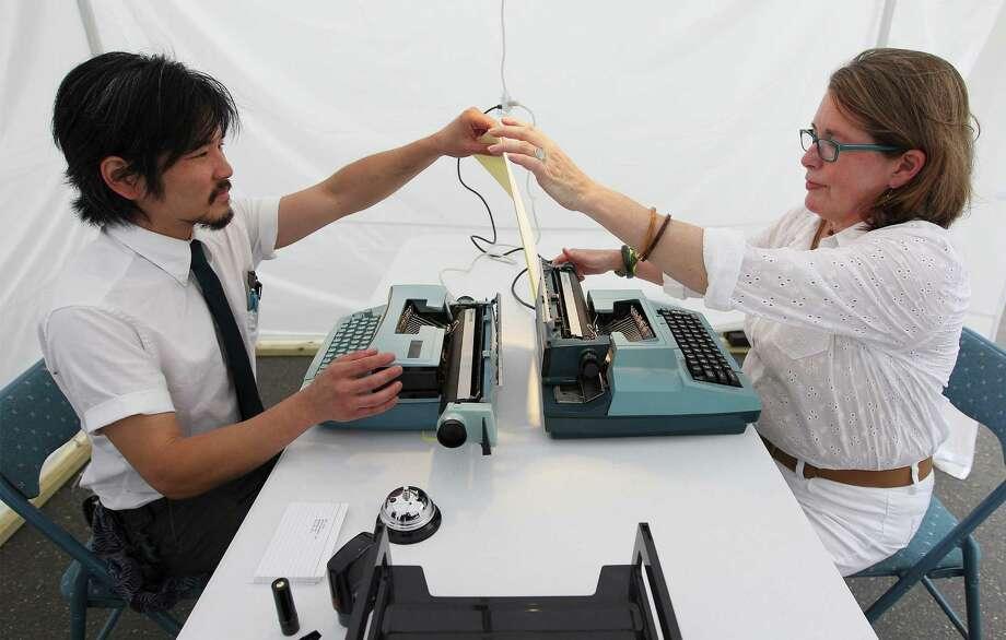 Artist Mat Kubo converses with Therese McDevitt using typewriters during the La Carpa art exhibit during the King William Fair on Saturday, Apr. 26, 2014. Photo: Kin Man Hui, San Antonio Express-News / ©2014 San Antonio Express-News