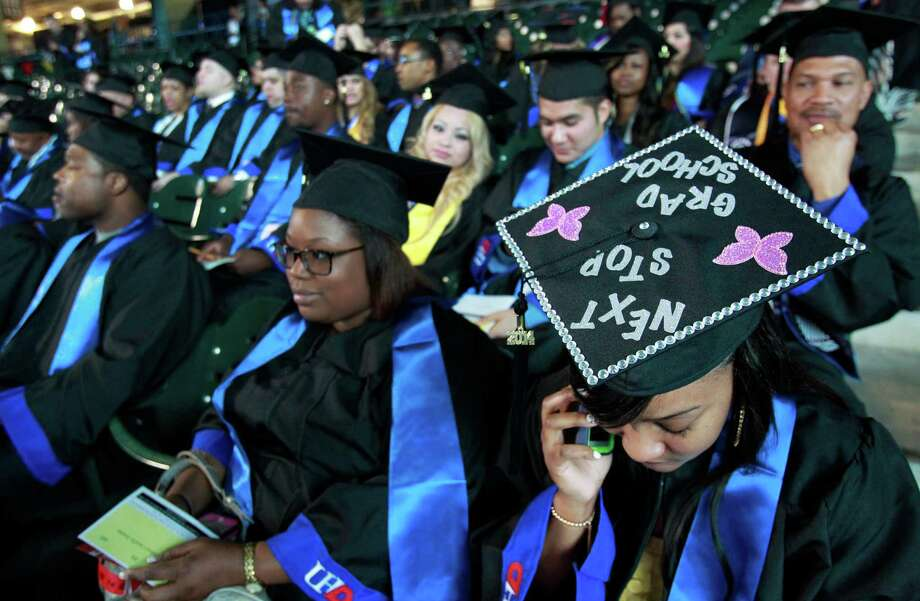 Lawanda Jones, right, of Houston and a criminal justice major, talks on the phone as she and other University of Houston Downtown students wait to begin commencement ceremony at Minute Maid Park Saturday, May 10, 2014, in Houston. Photo: Melissa Phillip, Houston Chronicle / © 2014  Houston Chronicle
