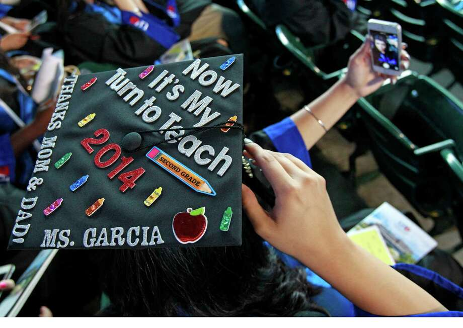 Aremy Garcia of Houston an education major takes a self portrait as she and other University of Houston Downtown students wait to begin commencement ceremony at Minute Maid Park Saturday, May 10, 2014, in Houston. Photo: Melissa Phillip, Houston Chronicle / © 2014  Houston Chronicle
