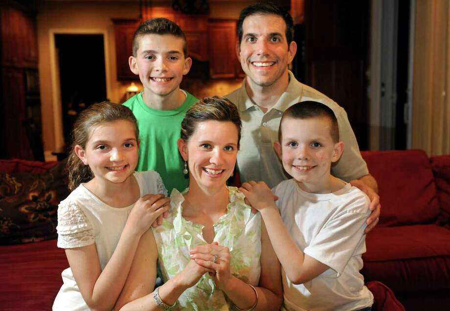 Christy Bunkoff, the 2013 Tulip Festival Mother of the Year, center, with her husband, Nathan Bunkoff, and their children on Thursday, May 1, 2014, at their home in Colonie, N.Y. From left are Emma Bunkoff, 11, Addison Bunkoff, 13, and Connor Bunkoff, 10. (Cindy Schultz / Times Union) Photo: Cindy Schultz / 00026707A