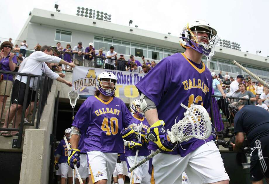 "The UAlbany Great Danes enter the field under a banner that says ""UAlbany will Shock The World TODAY"" before the game against Loyola in the NCAA Tournament at Ridley Athletic Complex in Baltimore on Saturday, May 10, 2014. (Brian Schneider / www.ebrianschneider.com) Photo: Brian Schneider / Brian Schneider"