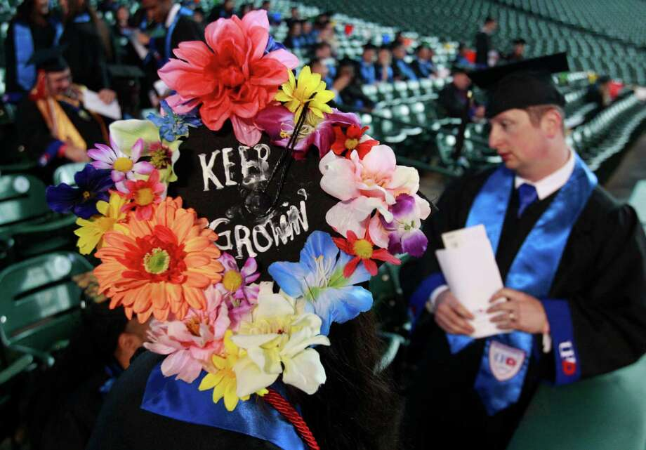 "Nadia Al-Khalifah, of Tucson, AZ and a fine art major decorated her graduation cap with ""Keep Growin' "" shown as she and other University of Houston Downtown students wait to begin commencement ceremony at Minute Maid Park Saturday, May 10, 2014, in Houston. Photo: Melissa Phillip, Houston Chronicle / © 2014  Houston Chronicle"