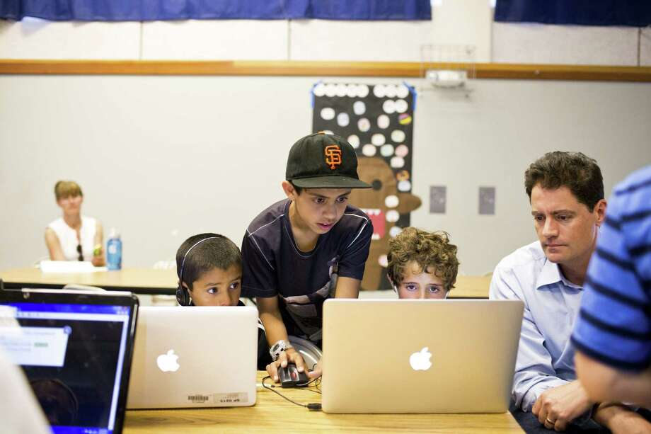 Imran Khaliq (center), a 12-year-old who knows Java and HTML, helps his brother Farhan, 7 (left), and Aidan Brown, 6, at a free event put on by Code.org at an elementary school in Mill Valley, Calif. Photo: Jason Henry / New York Times / NYTNS