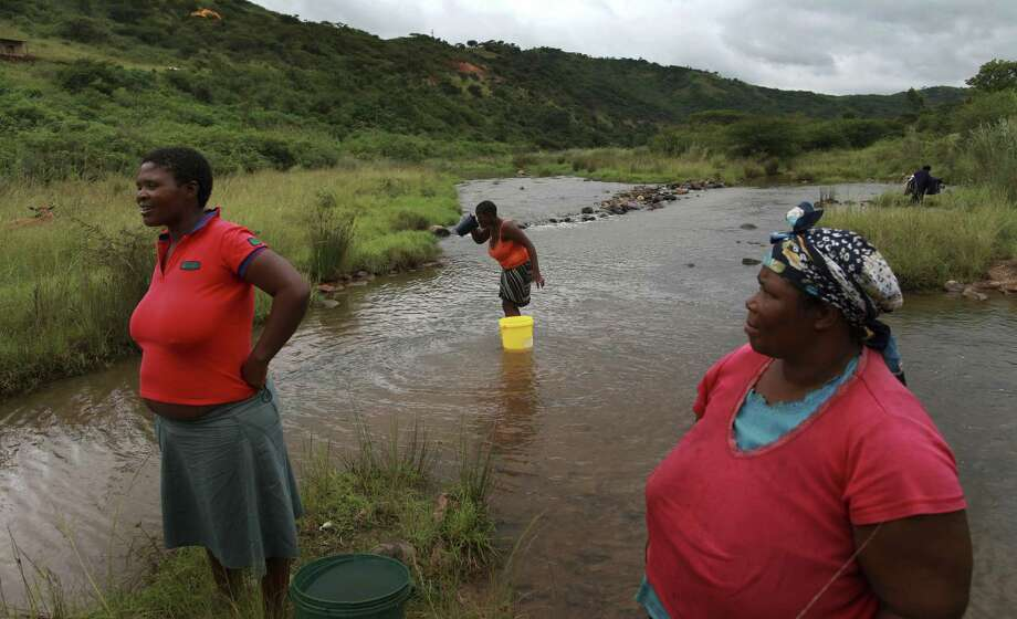 Women collect water from a stream in Ndwedwe, KwaZulu/Natal province, South Africa. A team of Norwegian gynecologists believes African women are more vulnerable to HIV because of a chronic, undiagnosed parasitic disease caused by worms picked up in infested river water. Photo: Joao Silva / New York Times / NYTNS