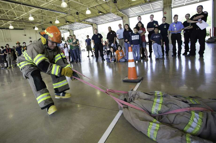 Marco Flores, 19, of the Brandeis High School Blazing Broncos Fire Explorers pulls a 165-pound dummy in the competition. Photo: J. Michael Short / For The San Antonio Express-News / Photo Copyright ©2014 J. MICHAEL SHORT