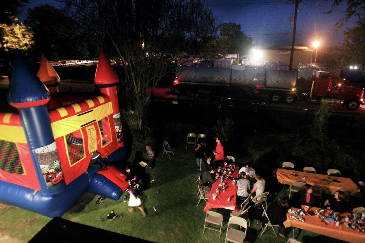 A truck drives by a container-cleaning business in Channelview, east of Houston, as neighbors celebrate a child's birthday across the street.
