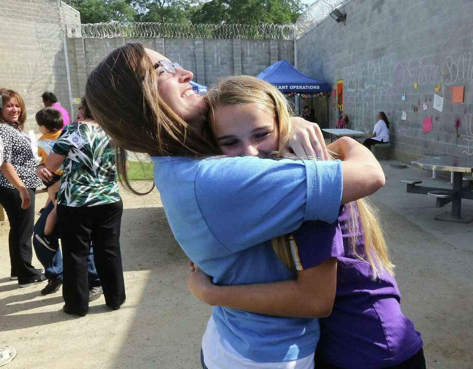 Inmate Tiffany Dugan (left) greets her daughter, Arianne Skelton, 13, with a hug at the Folsom Women's Facility in Folsom, Calif., in a visit facilitated by the Get on the Bus program. Photo: Rich Pedroncelli / Associated Press / AP